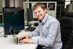 Молодой красивый смеясь над человек с компьютером в офисе Стоковые Фотографии RF