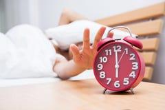 Молодой красивый спать и будильник женщины в спальне на hom Стоковые Фотографии RF