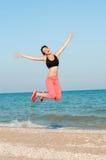 Молодой красивый спортсмен женщины скача на пляж Стоковые Изображения