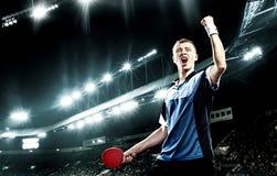 Молодой красивый спортсмен празднуя безупречную победу в настольном теннисе Стоковое фото RF
