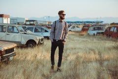 Молодой красивый стильный человек, нося рубашка и бабочка на поле старых автомобилей Стоковые Изображения