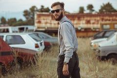 Молодой красивый стильный человек, нося рубашка и бабочка на поле старых автомобилей Стоковое фото RF