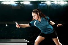 Молодой красивый теннисист женщины в игре на черной предпосылке Съемка действия стоковые изображения