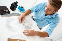 Молодой красивый уверенно задумчивый бизнесмен сидя на таблице с портретом чертежа карандаша Белый современный интерьер офиса Стоковая Фотография RF