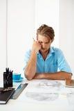 Молодой красивый уверенно задумчивый бизнесмен сидя на таблице думая над портретом чертежа карандаша самомоднейшая белизна офиса Стоковые Изображения RF