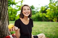 Молодой красивый усмехаться девушки, держа яблоко на пикнике в парке Стоковое Фото