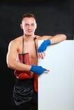 Молодой красивый человек боксера стоя близко доска, изолированная на черной предпосылке Стоковое Изображение
