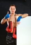 Молодой красивый человек боксера стоя близко доска и показывая о'кеы, изолированный на черной предпосылке Стоковые Фотографии RF