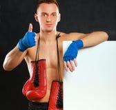 Молодой красивый человек боксера стоя близко доска и показывая о'кеы, на черной предпосылке Стоковые Фотографии RF