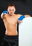 Молодой красивый человек боксера стоя близко доска и указывая на вас, изолированный на черной предпосылке Стоковая Фотография