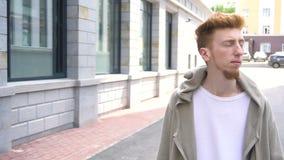 Молодой красивый человек в вскользь одеждах идя вдоль улицы видеоматериал