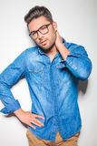 Молодой красивый человек в джинсовой ткани касаясь его шеи Стоковые Изображения