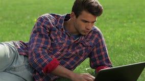Молодой красивый человек лежа на траве акции видеоматериалы