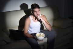 Молодой красивый человек есть попкорн крыто стоковые фотографии rf
