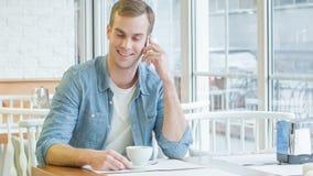 Молодой красивый человек имеет беседу телефона видеоматериал
