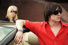 Молодой красивый человек моды в солнечных очках готовя его автомобиль Стоковое Изображение