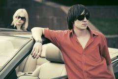 Молодой красивый человек около нового обратимого автомобиля стоковое фото rf