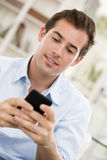 Молодой красивый человек писать SMS на мобильном телефоне. стоковое изображение