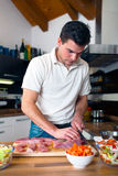 Молодой красивый человек подготавливая обед стоковое изображение