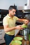 Молодой красивый человек подготавливая обед стоковые изображения