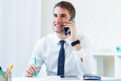 Молодой красивый человек работая в его офисе с мобильным телефоном Стоковая Фотография RF