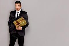 Молодой красивый человек с подарком стоковое изображение rf