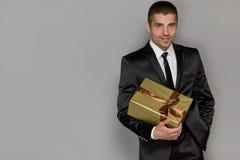 Молодой красивый человек с подарком стоковое фото