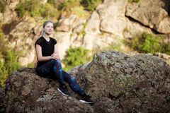 Молодой красивый sportive усмехаться девушки, сидя на утесе в каньоне Стоковые Фото