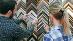 Молодой клиент пар ища рамка для изображения в atelier Стоковое Изображение RF