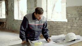 Молодой мастер стоя на строительной площадке и рисуя на светокопии конструкции Гражданский инженер работает с акции видеоматериалы