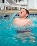 Молодой мальчик брызгая в бассейн Стоковая Фотография RF