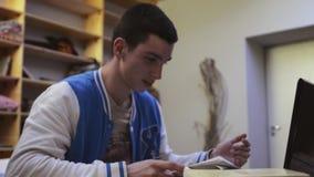 Молодой мальчик в взгляде куртки над листами бумаги, радостно сидит назад на стуле и протягивать Студент акции видеоматериалы