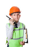 Молодой мальчик в защитном шлеме и жилете говорит к портативному радио Стоковые Фотографии RF