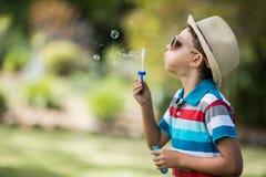 Молодой мальчик в солнечных очках дуя пузыри через палочку пузыря Стоковые Изображения