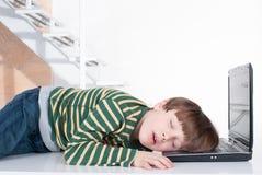 Молодой мальчик лежа на портативном компьютере Стоковые Фотографии RF