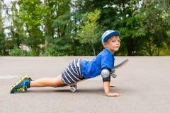 Молодой мальчик лежа на скейтборде в вымощенной серии стоковые фото
