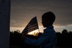 Молодой мальчик держа американский флаг, признательный для свободы стоковая фотография rf