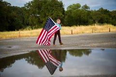 Молодой мальчик держа большой американский флаг показывая патриотизм для его собственной страны, соединяет положения стоковые изображения rf
