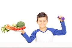 Молодой мальчик держа плиту полный овощей и гантели Стоковые Изображения RF