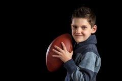Молодой мальчик держа футбол любит защитник Стоковая Фотография