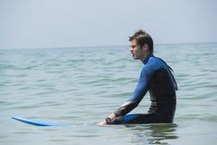 Молодой мальчик занимаясь серфингом в море, ждать развевает Стоковые Изображения RF