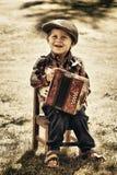 Молодой мальчик играя аккордеон стоковая фотография