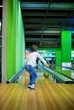 Молодой мальчик, играя боулинг внутри помещения стоковая фотография rf