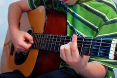 Молодой мальчик играя гитару стоковое фото
