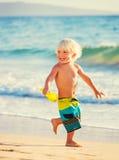 Молодой мальчик играя на пляже стоковые фото