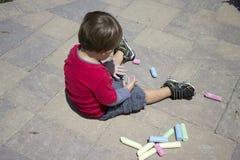Молодой мальчик играя с мелом Стоковая Фотография RF