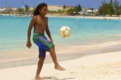 Молодой мальчик играя футбол на пляже в Барбадос, карибских стоковые фотографии rf
