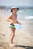 Молодой мальчик играя шарик затвора на солнечном пляже стоковое изображение