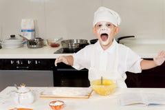 Молодой мальчик имея потеху в кухне стоковые изображения rf