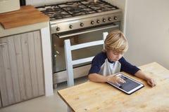 Молодой мальчик используя планшет в кухне, повышенном взгляде Стоковое Фото